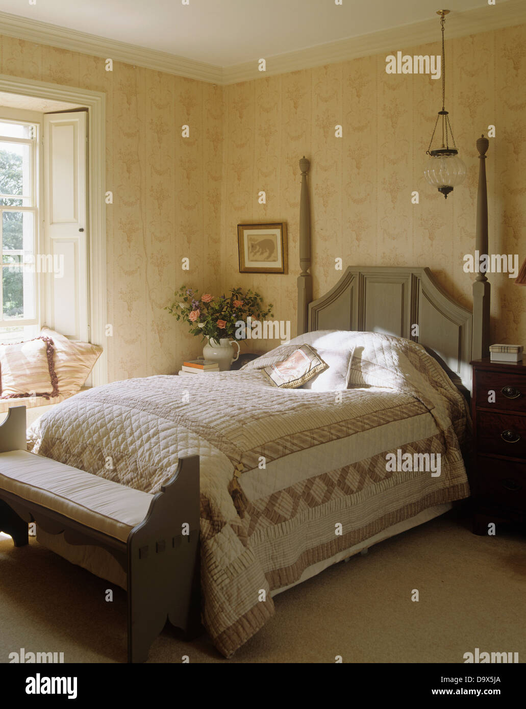 Gray Patchwork Quilt On Gray Painted Bed With Tall Posts On Headboard Stock Photo Alamy