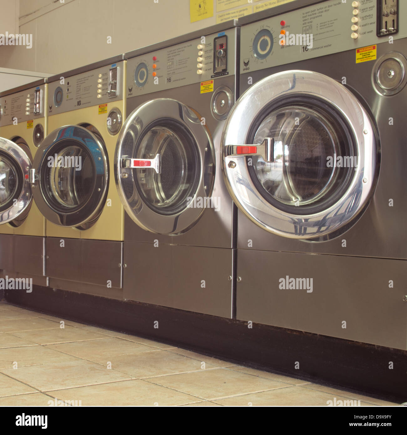 Row of coin operated stainless steel washing machines in Laundrette - Stock Image
