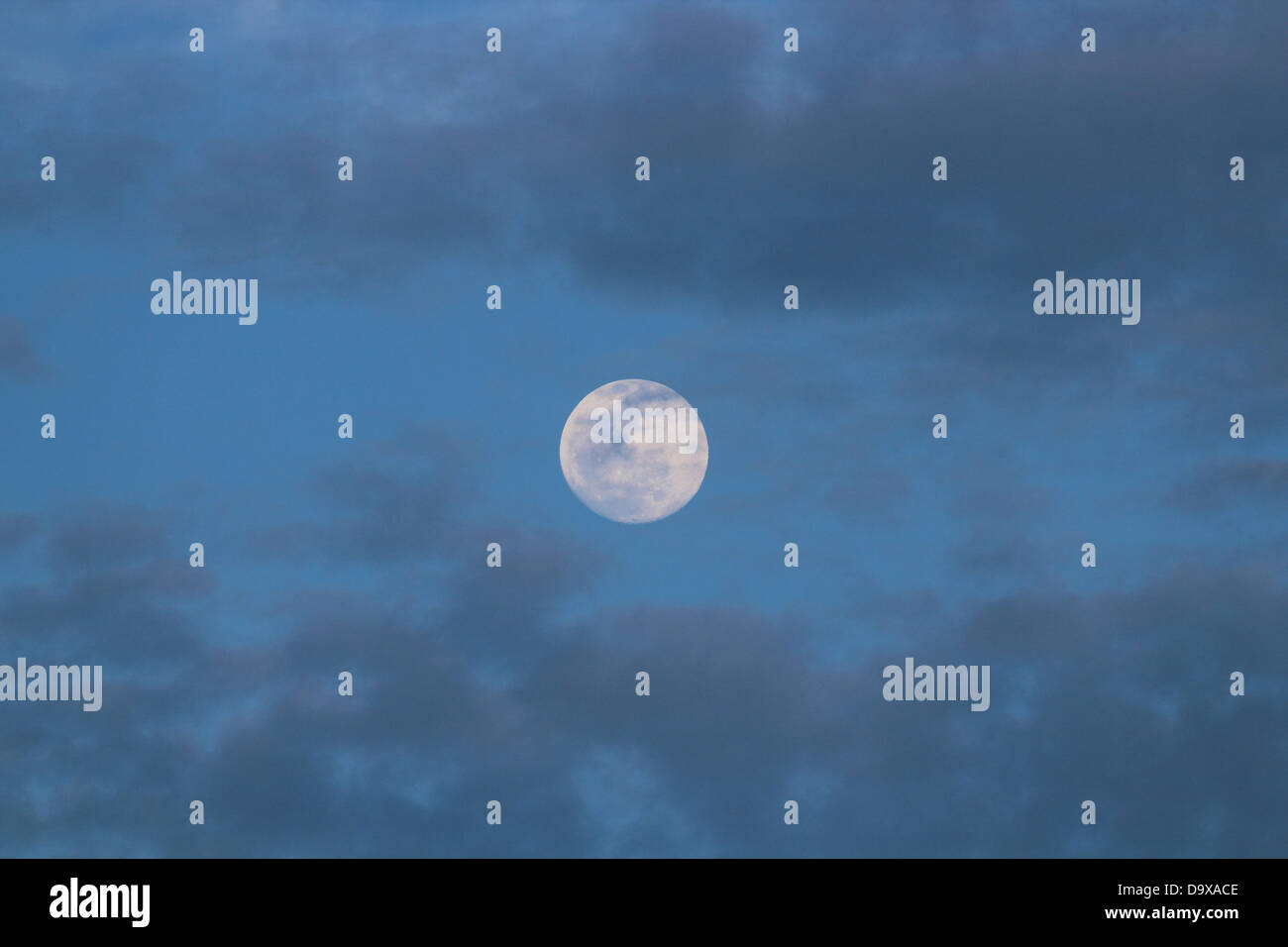 Full moon in a blue sky with some clouds Stock Photo