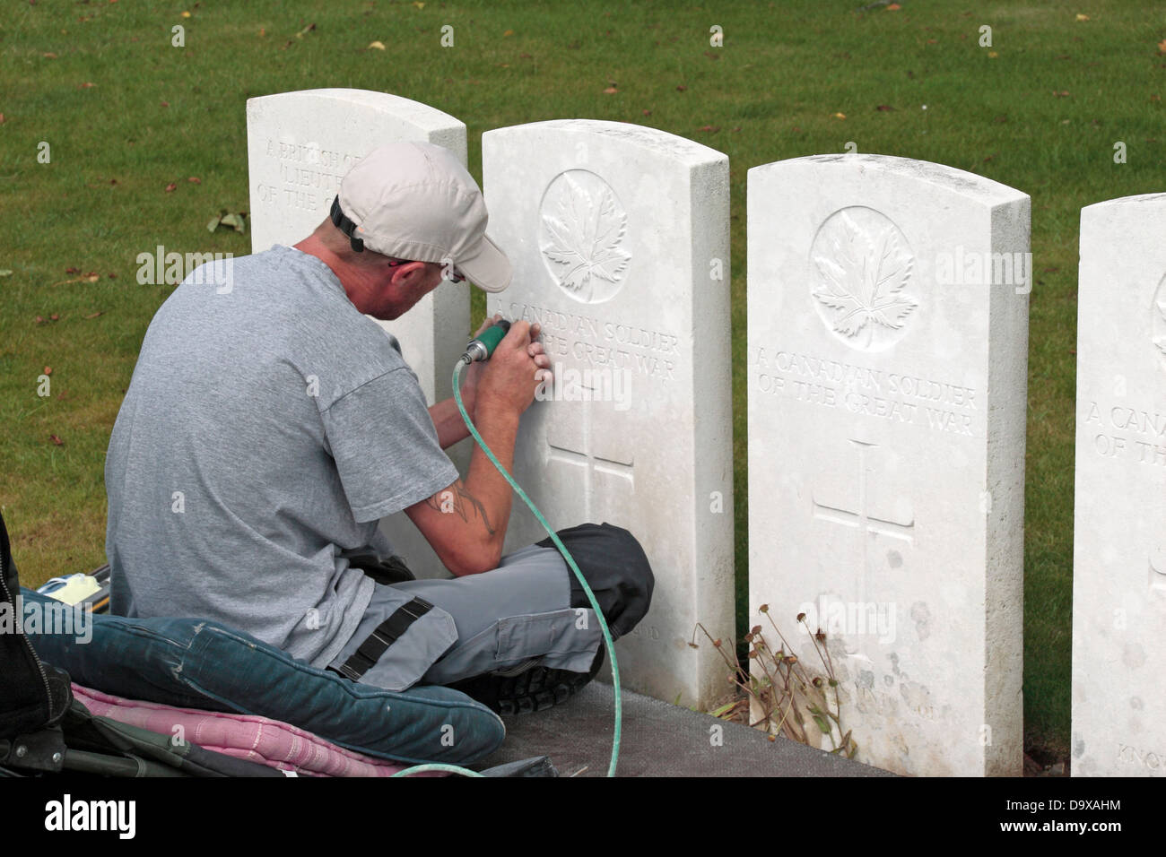Engraver repairing on a headstone in the CWGC Ovillers Military Cemetery, near Albert ,Somme, Picardy, France. - Stock Image