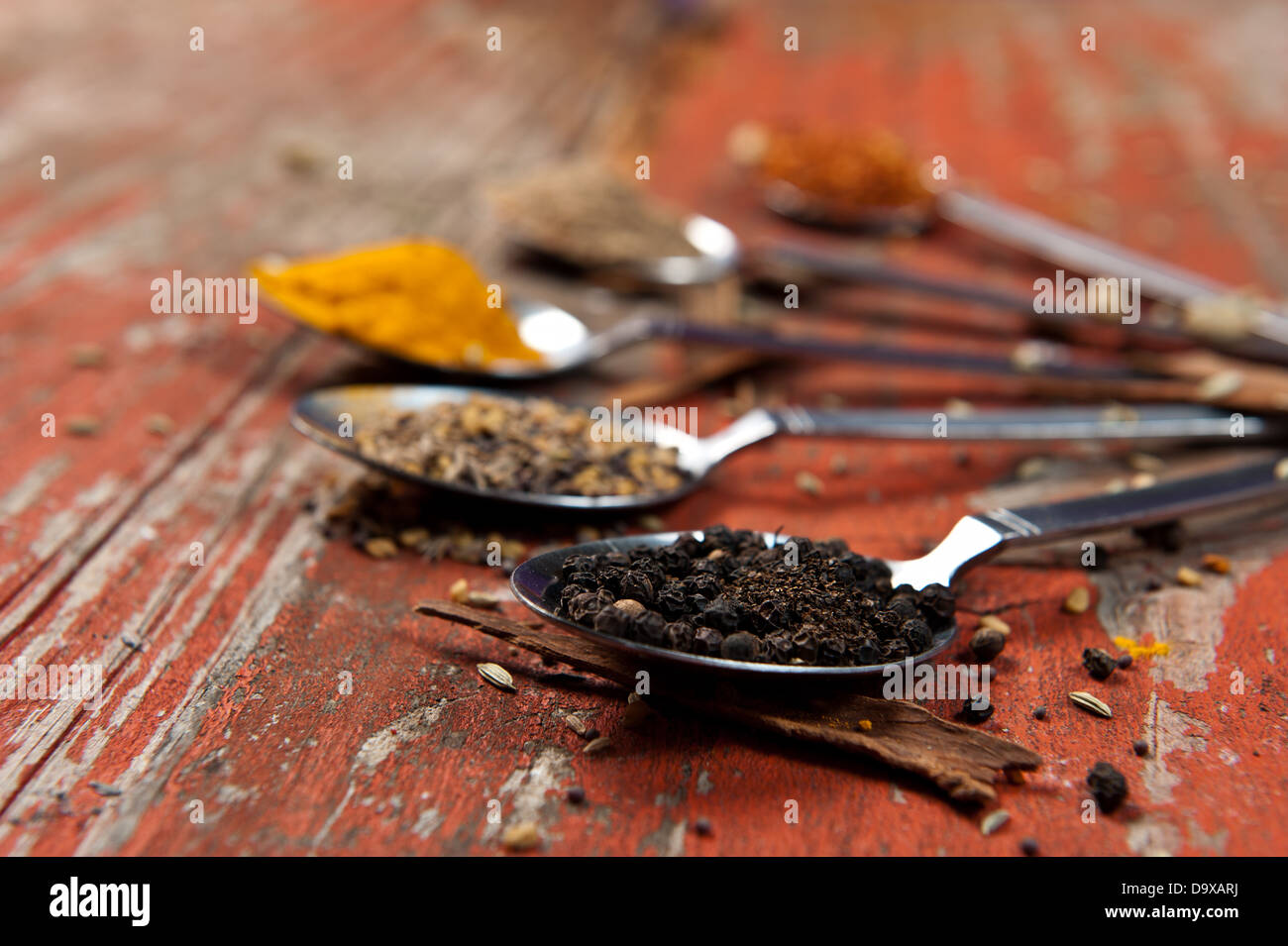 Table spoons heaped with different spices on an orange textured wooden surface. Artistic use of shallow depth of - Stock Image