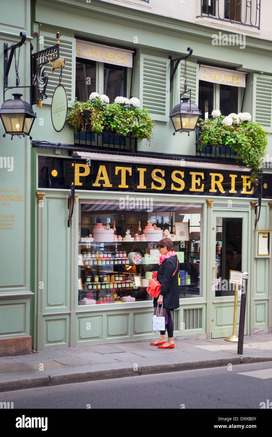 Woman window shoping at Laduree Patisserie in Saint German des Pres, Paris France - Stock Image