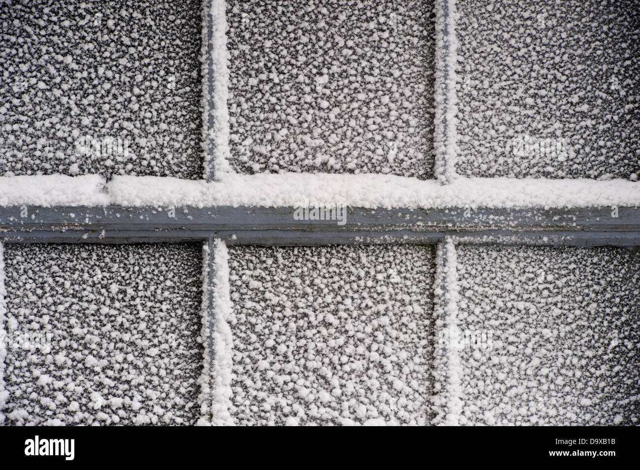 Snow on a barn window pane. - Stock Image