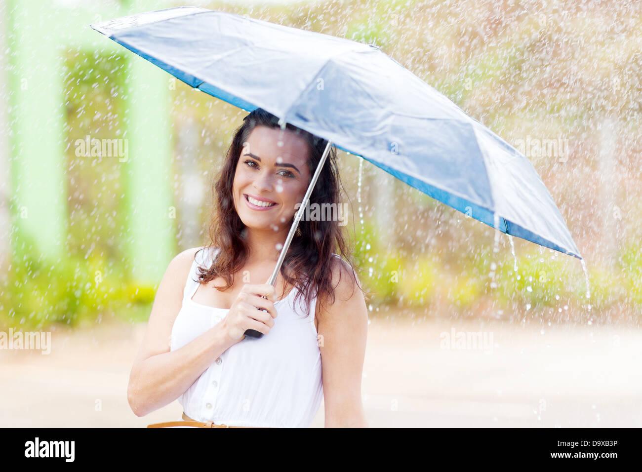pretty young woman in the rain with umbrella - Stock Image