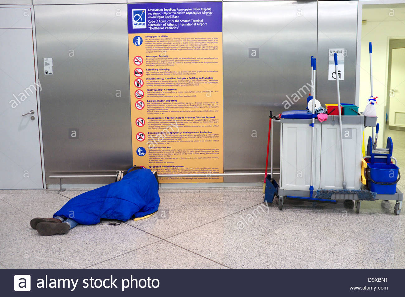 Greek economic crisis - homeless man sleeping by the toilet entrancehom in Athens International Airport 'Eleftherios - Stock Image