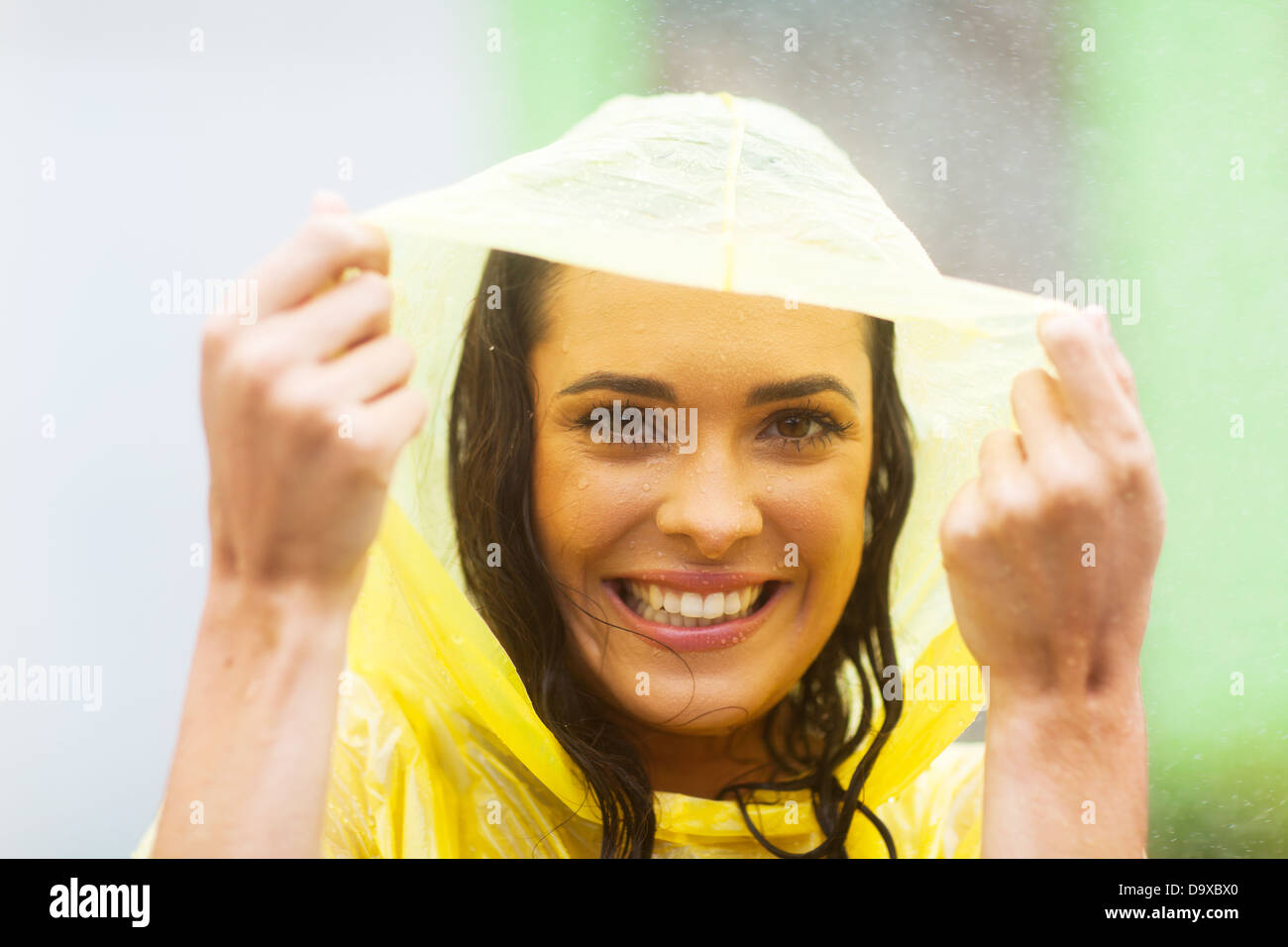 happy young woman in poncho in the rain - Stock Image