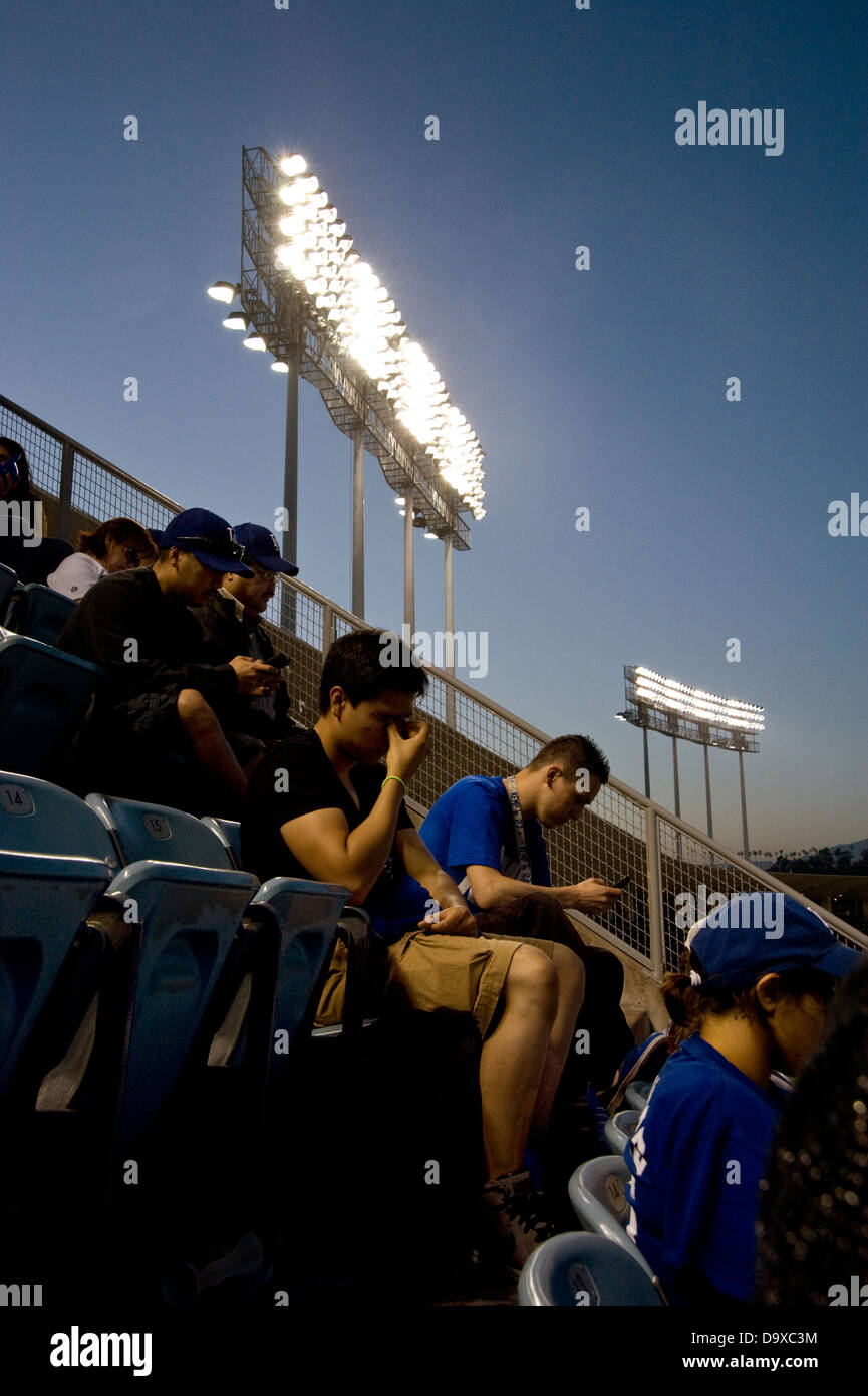 Fans at a sporting event using cell phones and texting - Stock Image