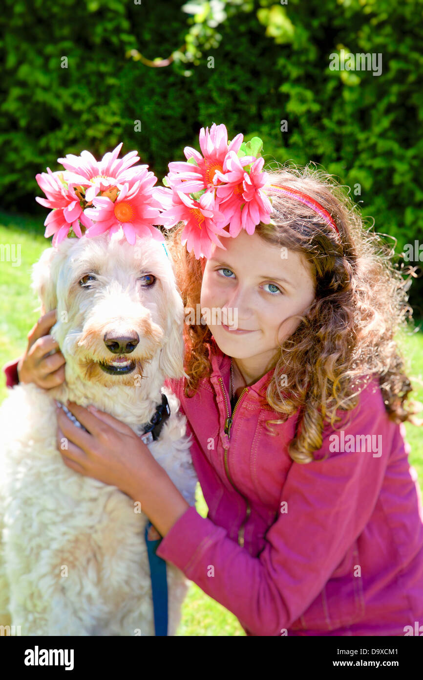 Teen girl and white dog wearing flowers Stock Photo