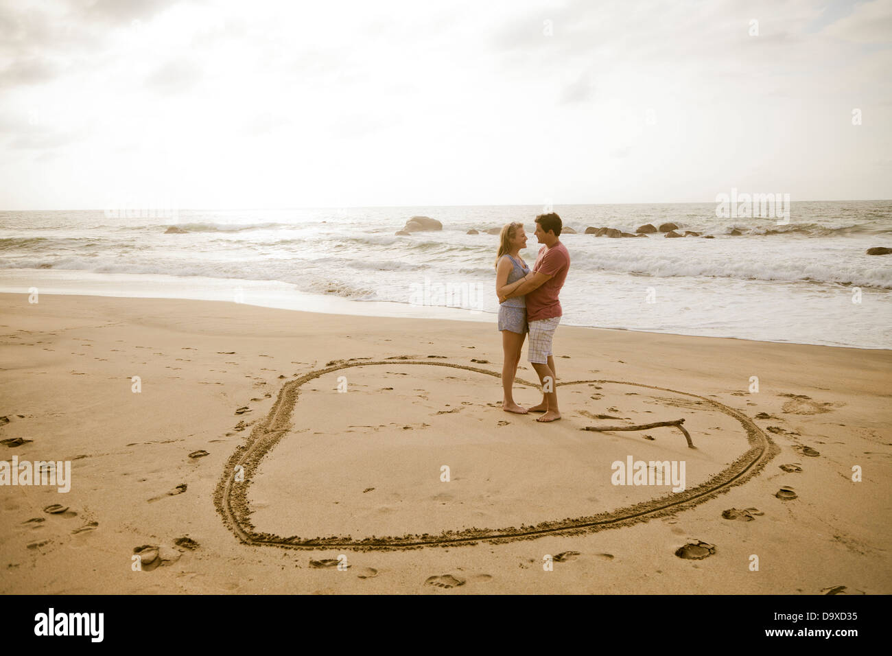 Young couple standing in heart design on beach - Stock Image