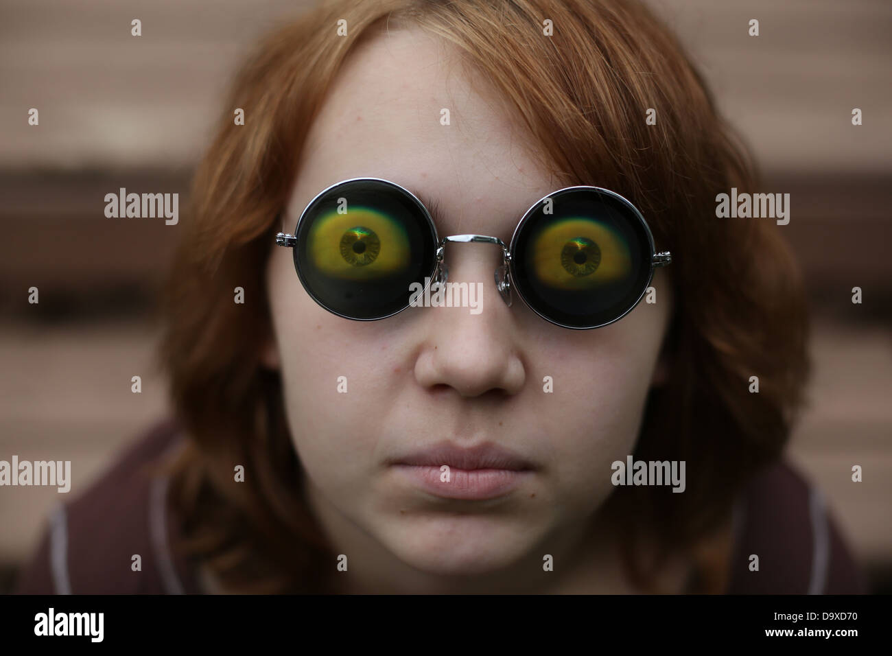 A teenage girl wearing funny eyeball glasses. - Stock Image