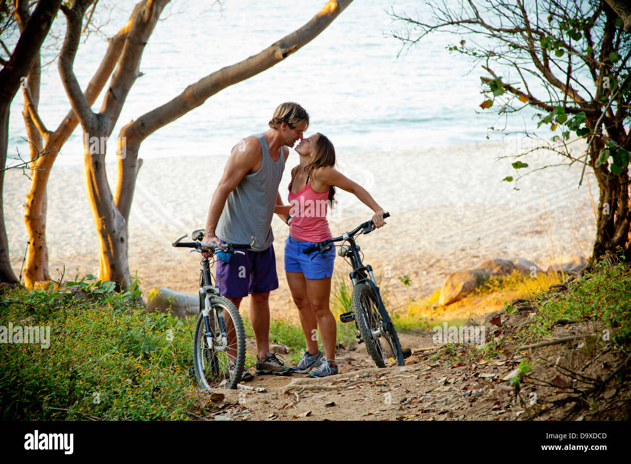 Couple riding bicycles on path to beach Stock Photo