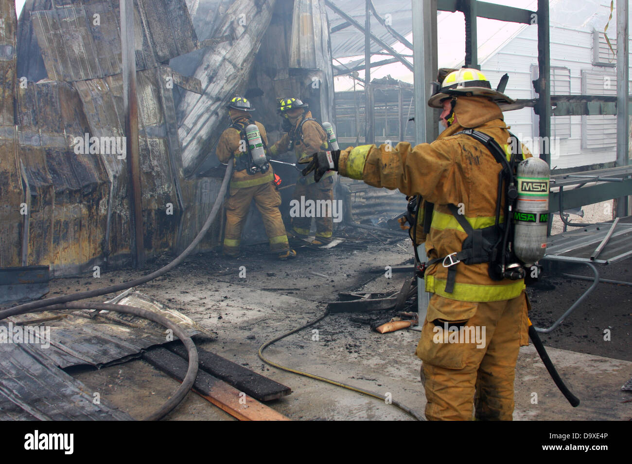 A chief giving directions as two firefighters extinguishing a fire - Stock Image