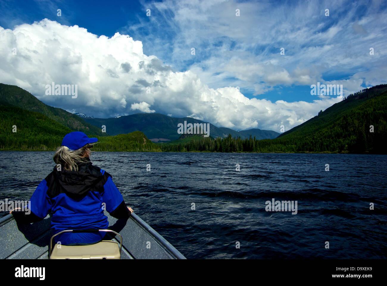 Woman sitting bow aluminum boat windy Muchalat Lake Vancouver Island BC - Stock Image