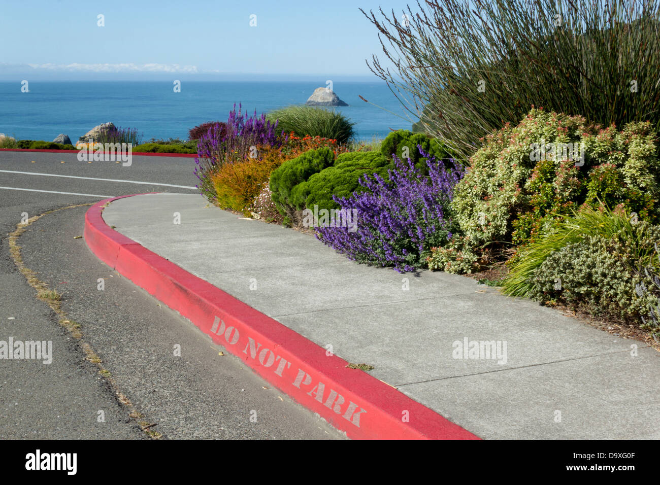 Red curb with no parking sign, fire lane. - Stock Image