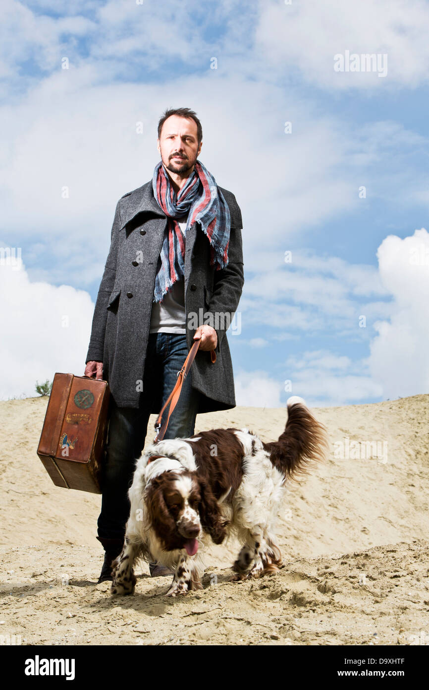 Germany, Bavaria, Man with dog standing in sand - Stock Image