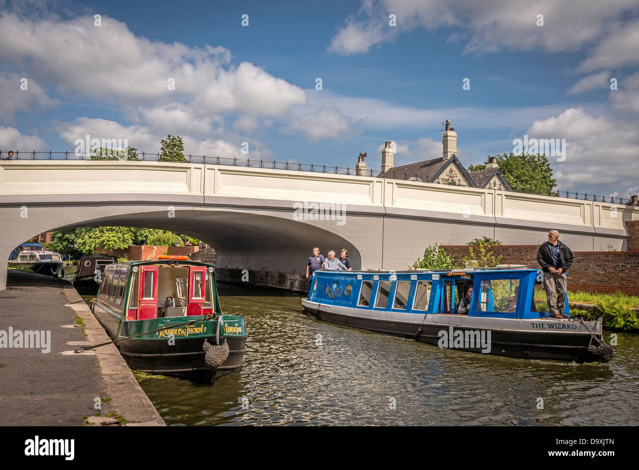 London Bridge carrying the A49 road over the Bridgewater canal and its narrowboats at Stockton Heath. - Stock Image