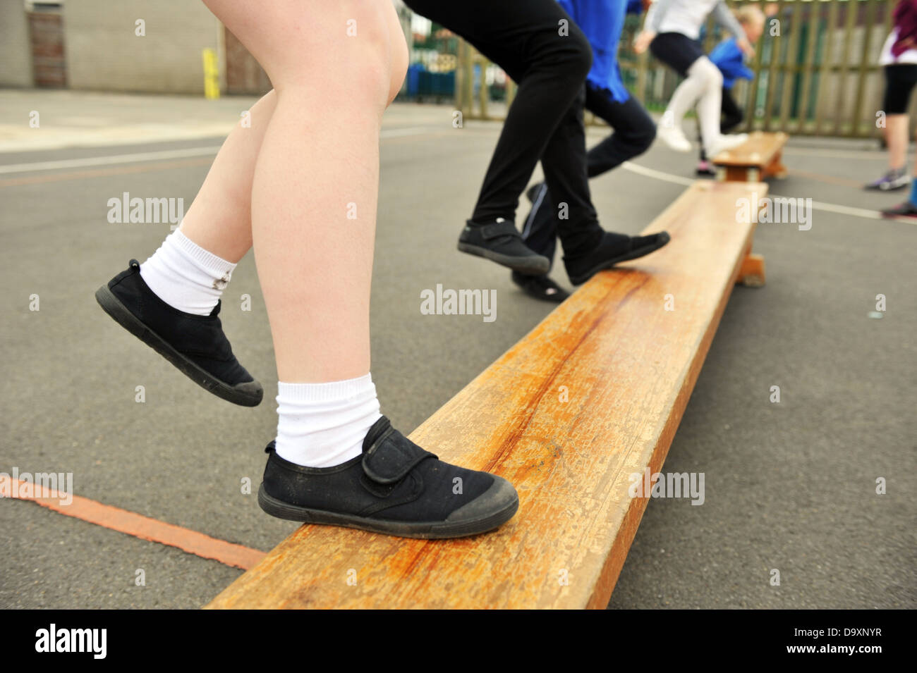 Close up of child's feet  wearing plimsolls in a P E Class UK School - Stock Image