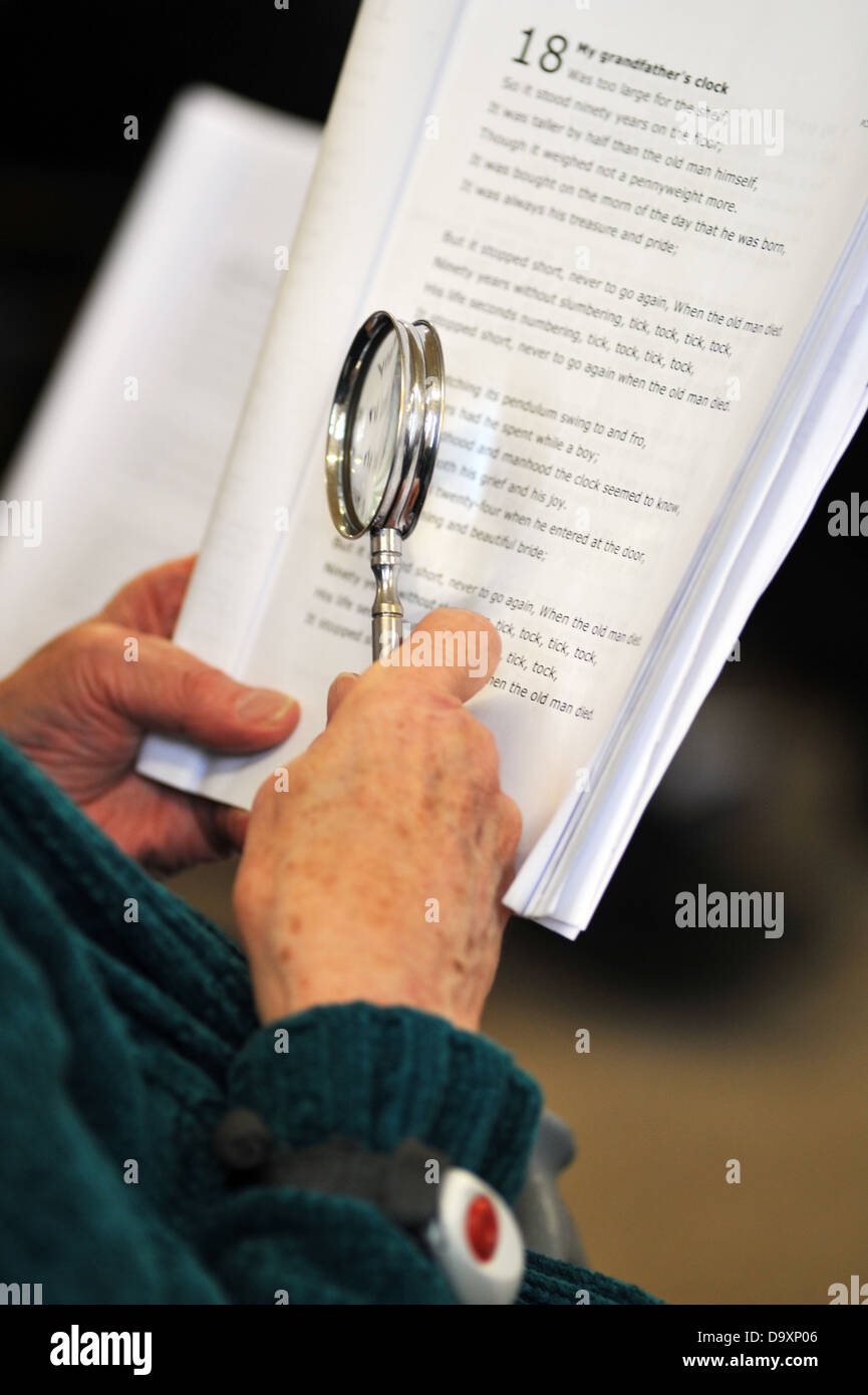 A woman with Dementia uses a magnifying glass to see the music at a Singing class for elderly people with dementia. - Stock Image