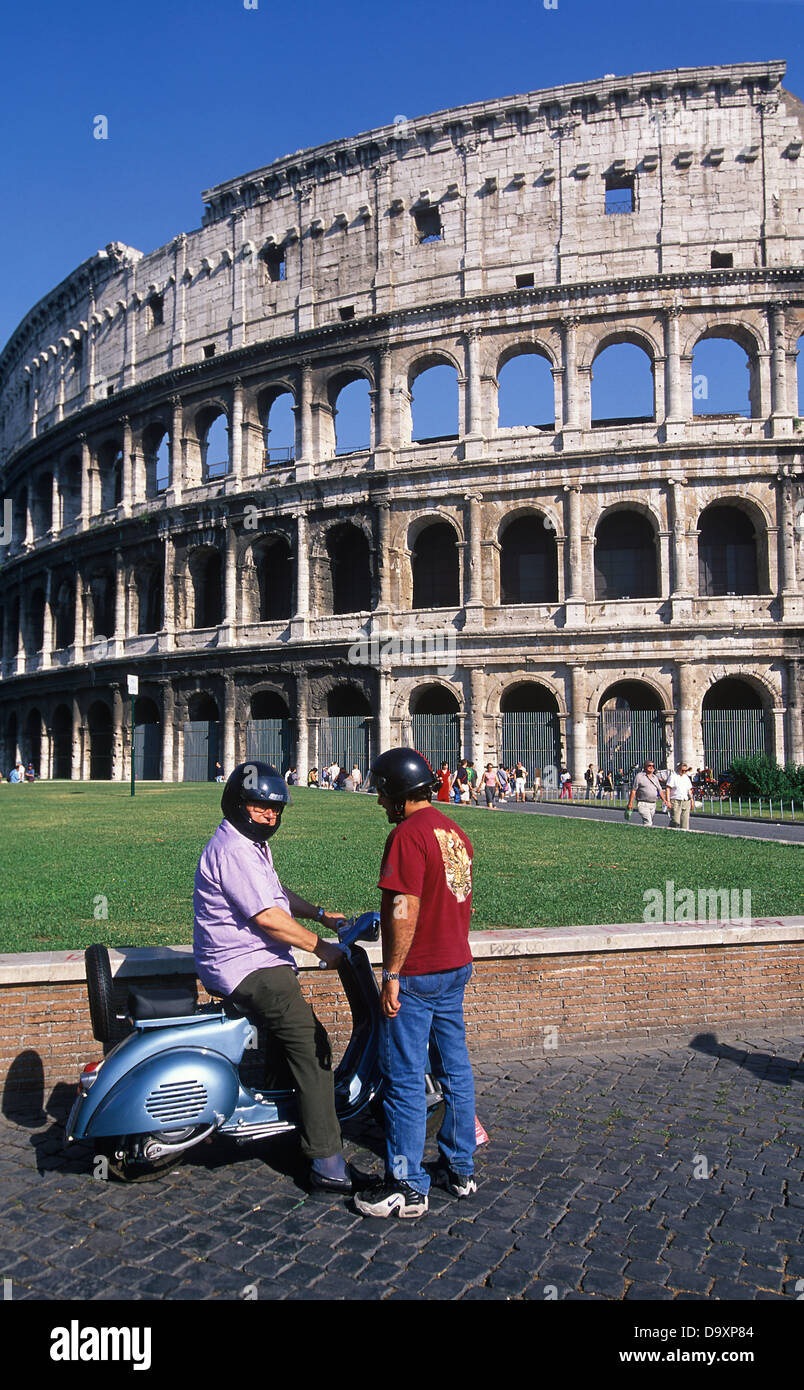 2 moped riders in helmets outside the Colosseum Rome Italy - Stock Image