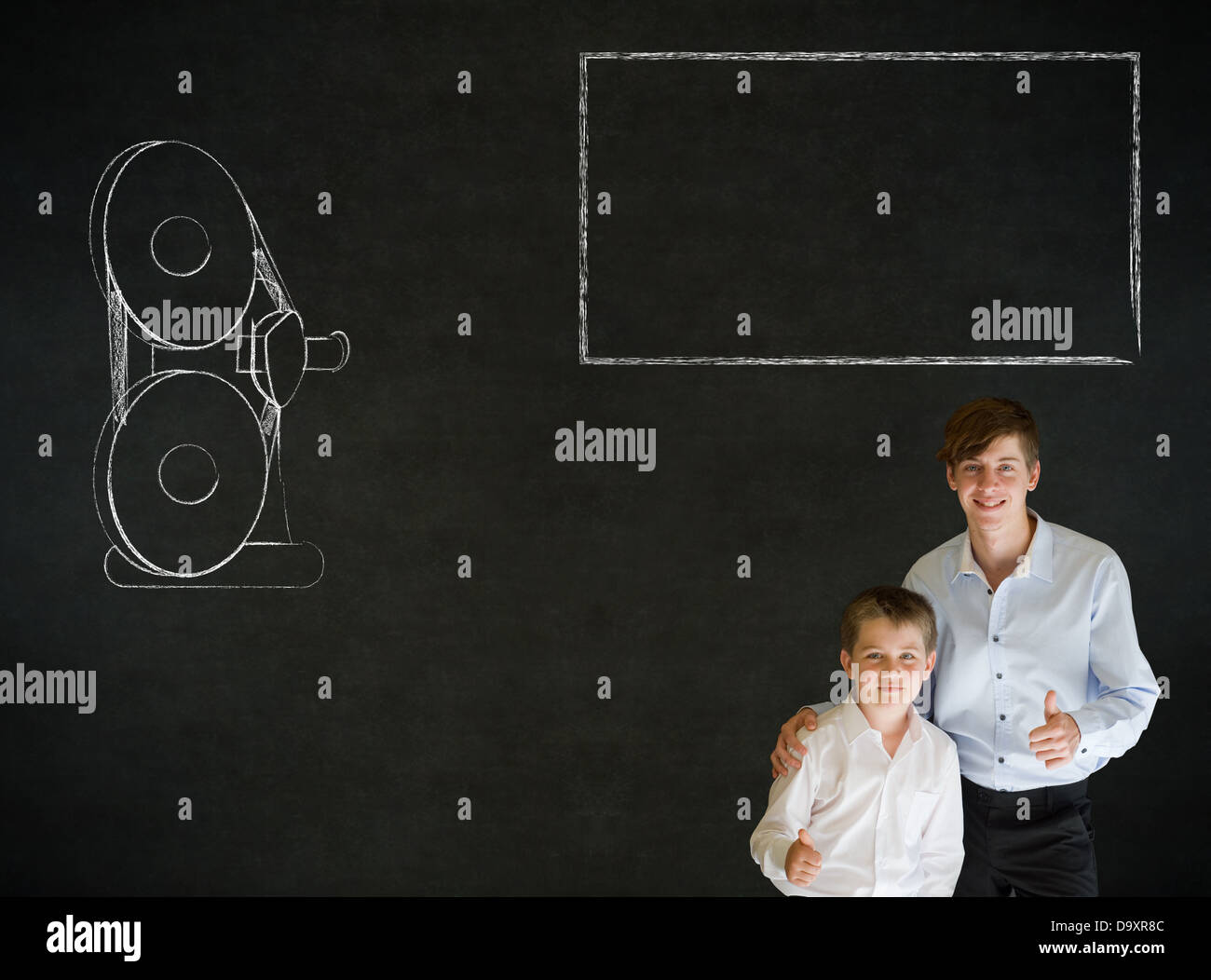 Thumbs up boy dressed up as business man with teacher man and retro chalk film projector on blackboard background Stock Photo