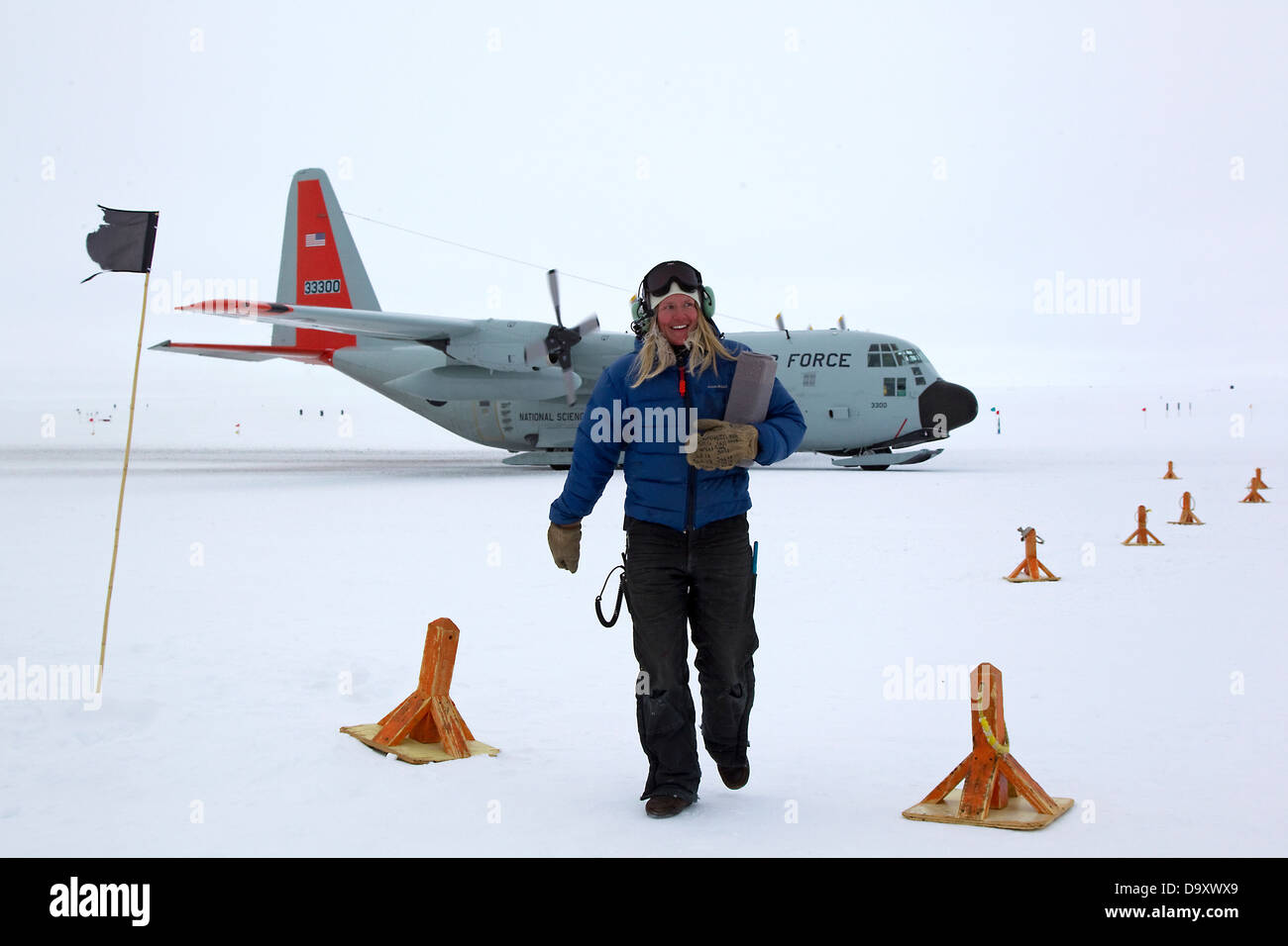 Female airstrip crew worker and C130 Hercules airplane at South Pole, Antarctica - Stock Image