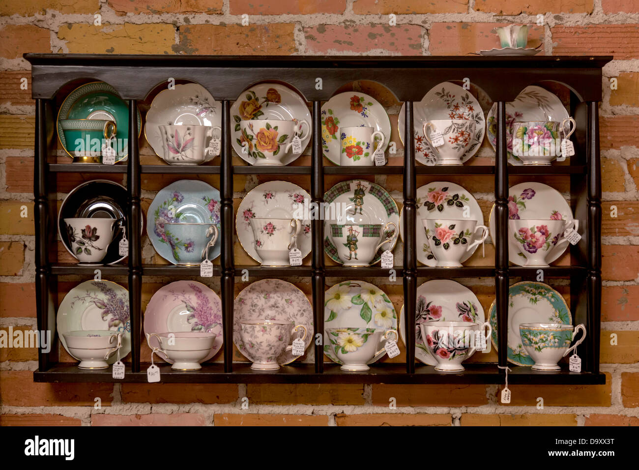 Antique China Tea Cups On Display In A Wooden Wall Mounted Cabinet.