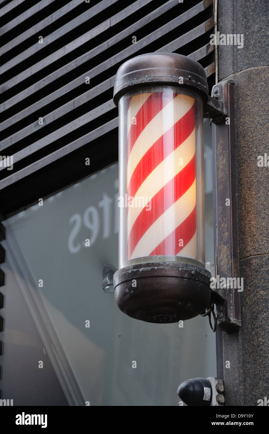 The red and white illuminated sign of a barbers shop in Glasgow. - Stock Image