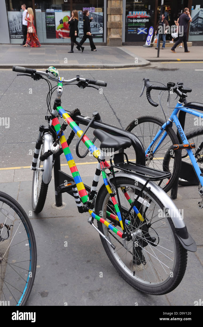 Coloured bikes secured at a bike stand - Stock Image