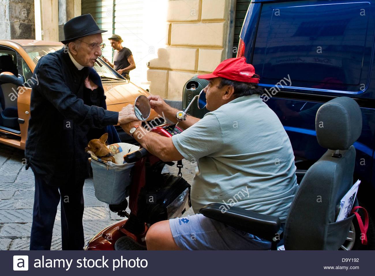 Don Andrea talking to a disabled person in the caruggi. Don Andrea Gallo,Genoa,Italy - Stock Image