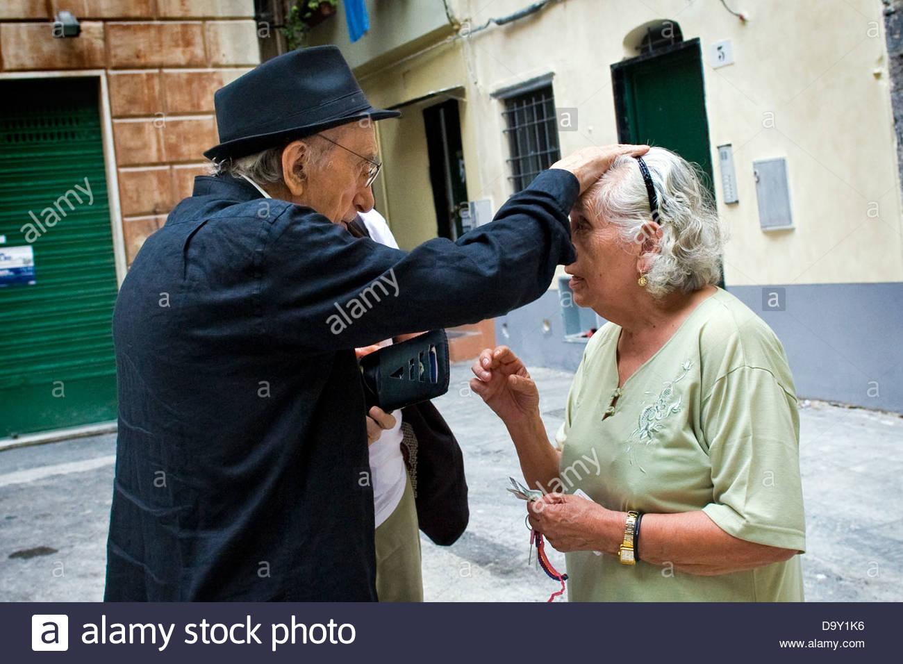 Don Andrea blesses a Peruvian woman. Don Andrea Gallo,Genoa,Italy - Stock Image