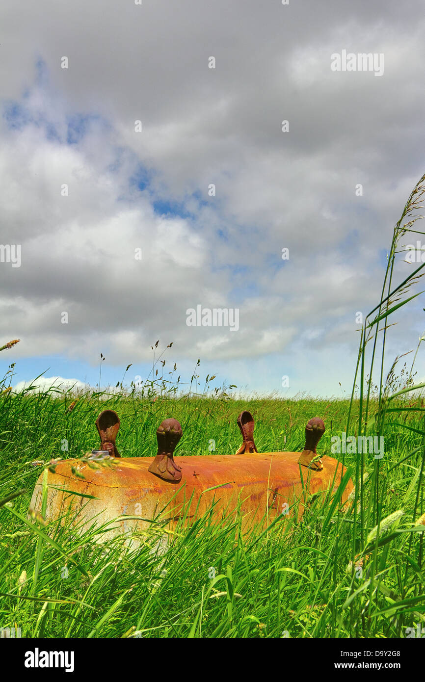 Upturned rusty old bath tub in a field - Stock Image