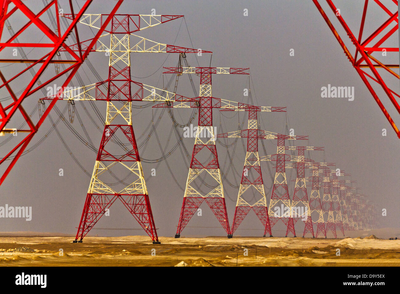 High voltage pylons in a perfect alignment crossing the desert. - Stock Image