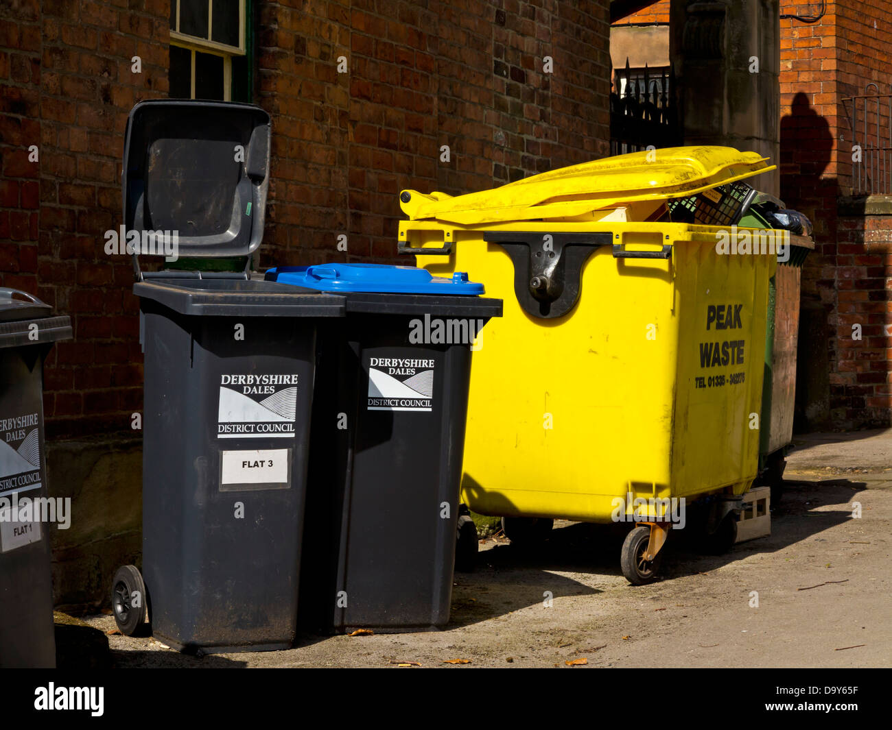 Black wheelie bins and yellow plastic skip used to collect domestic and commercial waste in a street in Wirksworth Stock Photo