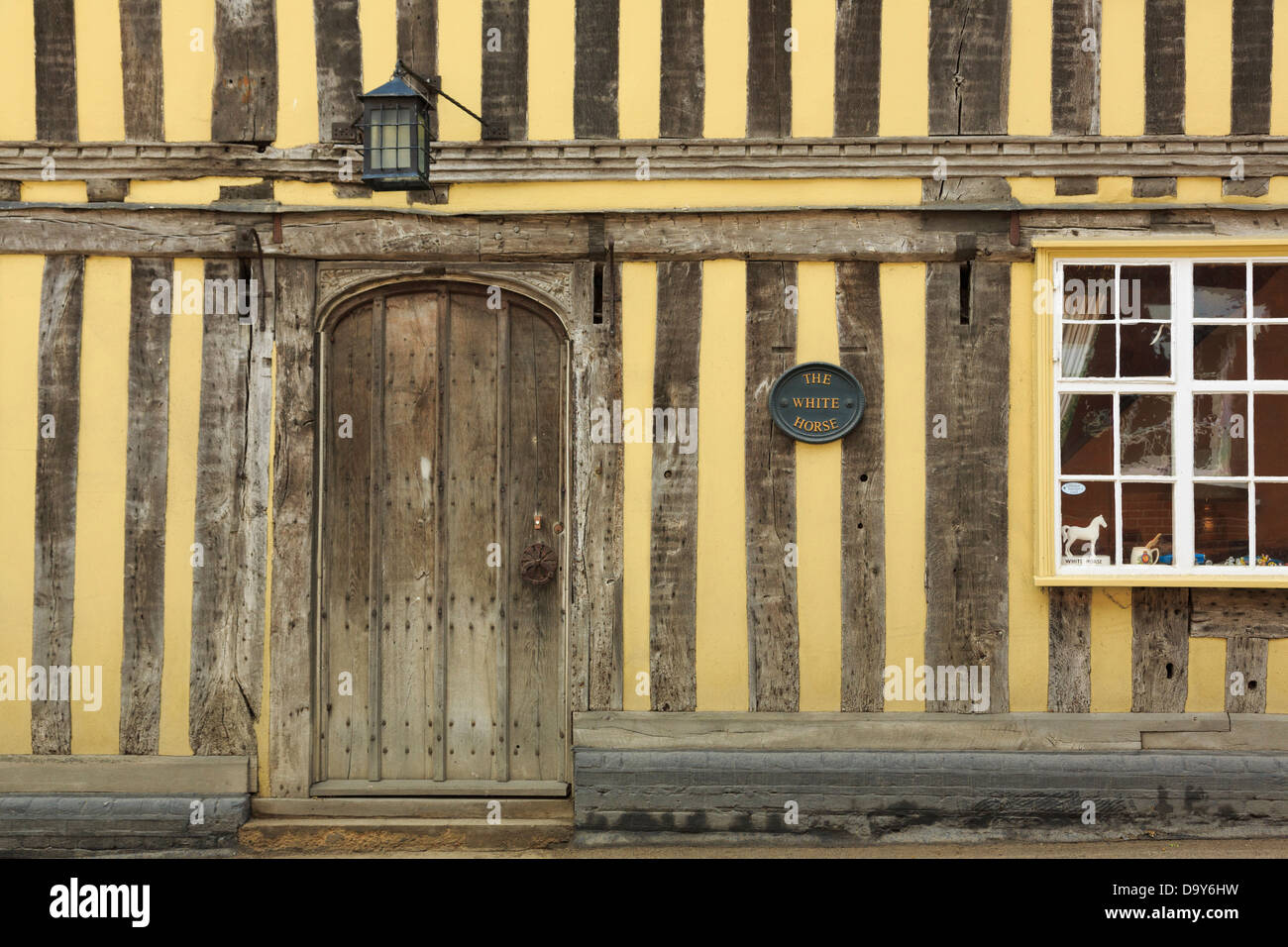Old wooden door in 15th century yellow timbered building formerly The White Horse inn in Lavenham, Suffolk, England, - Stock Image