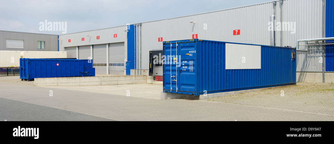 modern warehouse with containers and trucks in front - Stock Image
