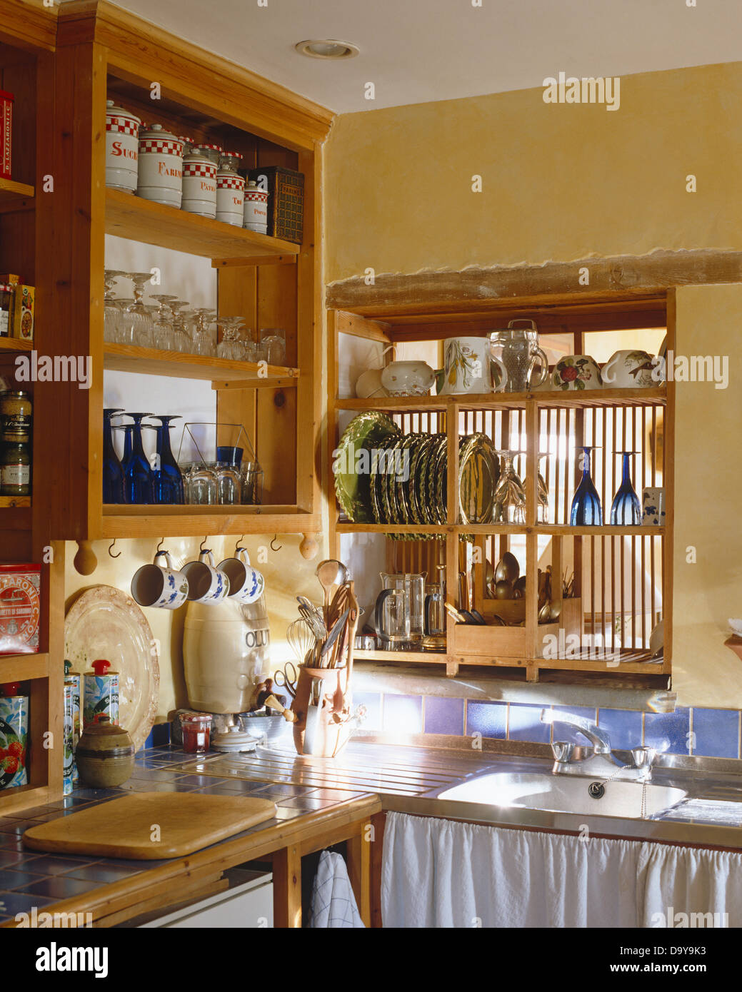 Storage jars on pine shelving in cottage kitchen with wooden plate rack used as ider above sink in unit with white drapes & Storage jars on pine shelving in cottage kitchen with wooden plate ...