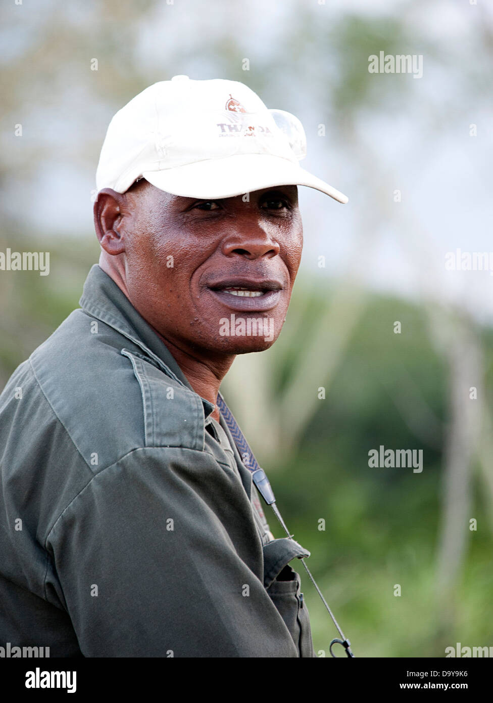 Portrait of African game reserve worker in white peaked cap. South Africa. - Stock Image