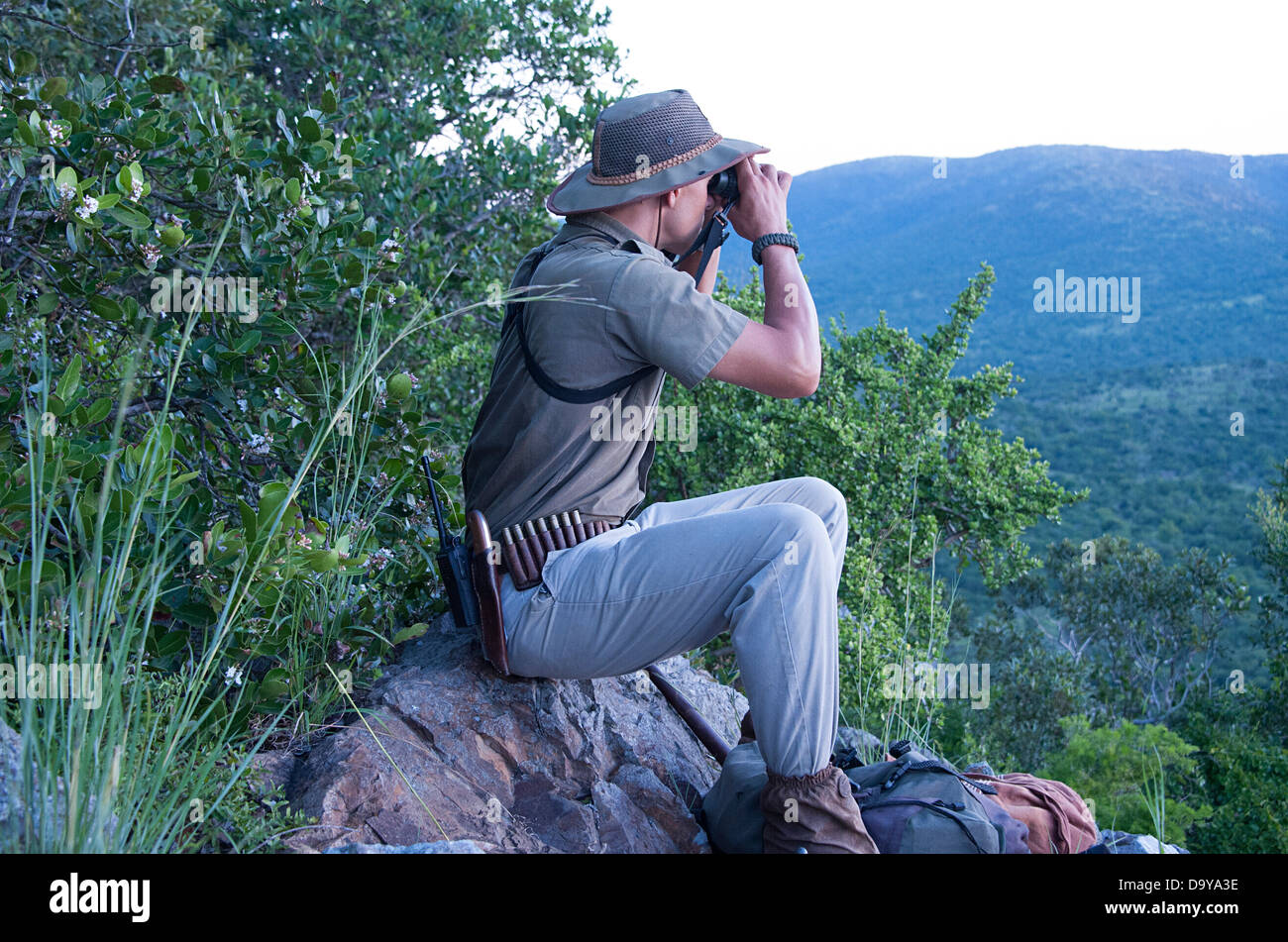 A guide surveys the view from the top of the climb. South Africa. - Stock Image