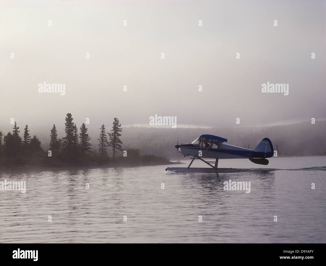 Lee Fink taxiing Piper Tri-Pacer as morning fog rolls over Hardenburg Bay Lake Clark National Park Preserve Port - Stock Image