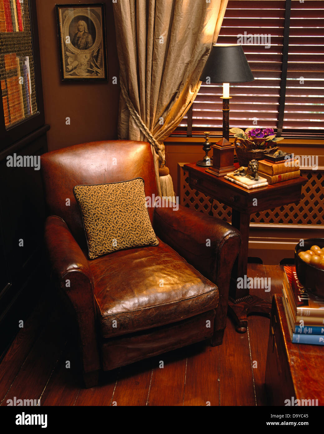 Brown Leather Armchair Next To Side Table With Lighted Lamp In Front Of  Window With Cream Silk Drapes And Wooden Venetian Blind