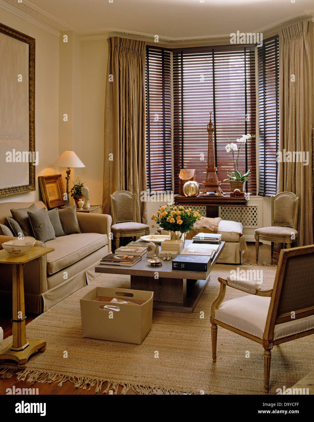 Beige sofa and leather storage box beside coffee table in living room with beige drapes and wooden Venetian blind on window & Beige sofa and leather storage box beside coffee table in living ...