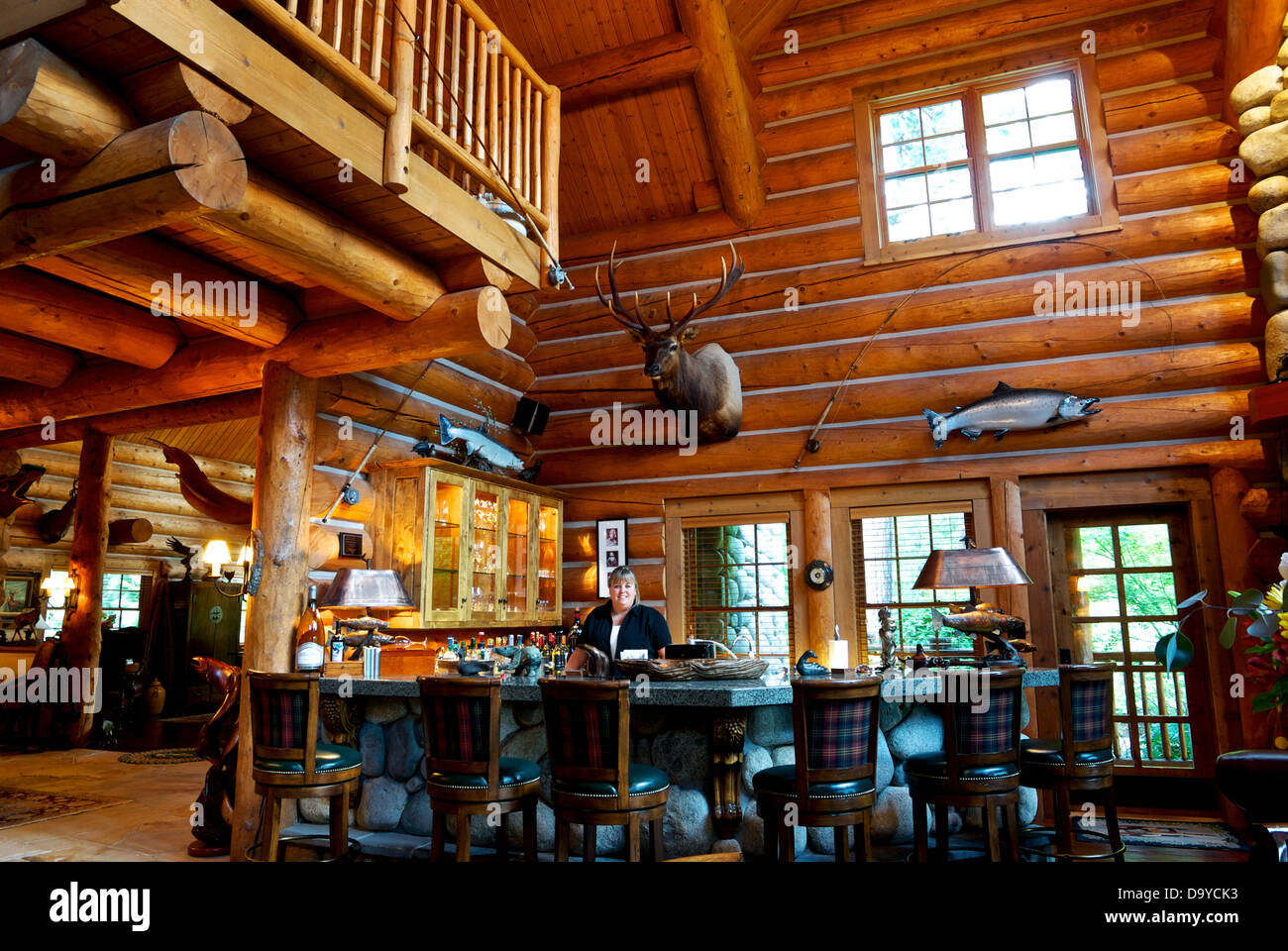 Bartender well stocked guest bar in games room at The Lodge at Gold River luxury fishing resort - Stock Image