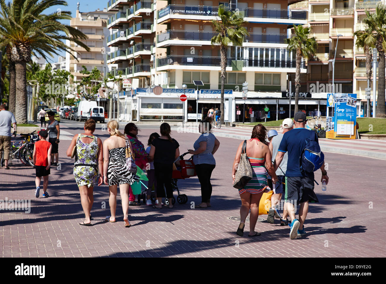 british and spanish holidaymakers walk along tree lined seafront promenade salou catalonia spain - Stock Image