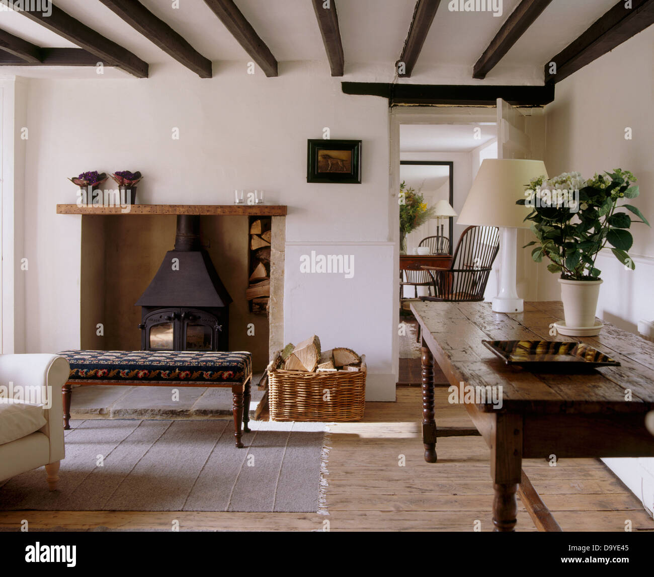Old Oak Table And Wooden Floor In White Cottage Living Room With  Upholstered Stool In Front Of Fireplace With Wood Burning Stove