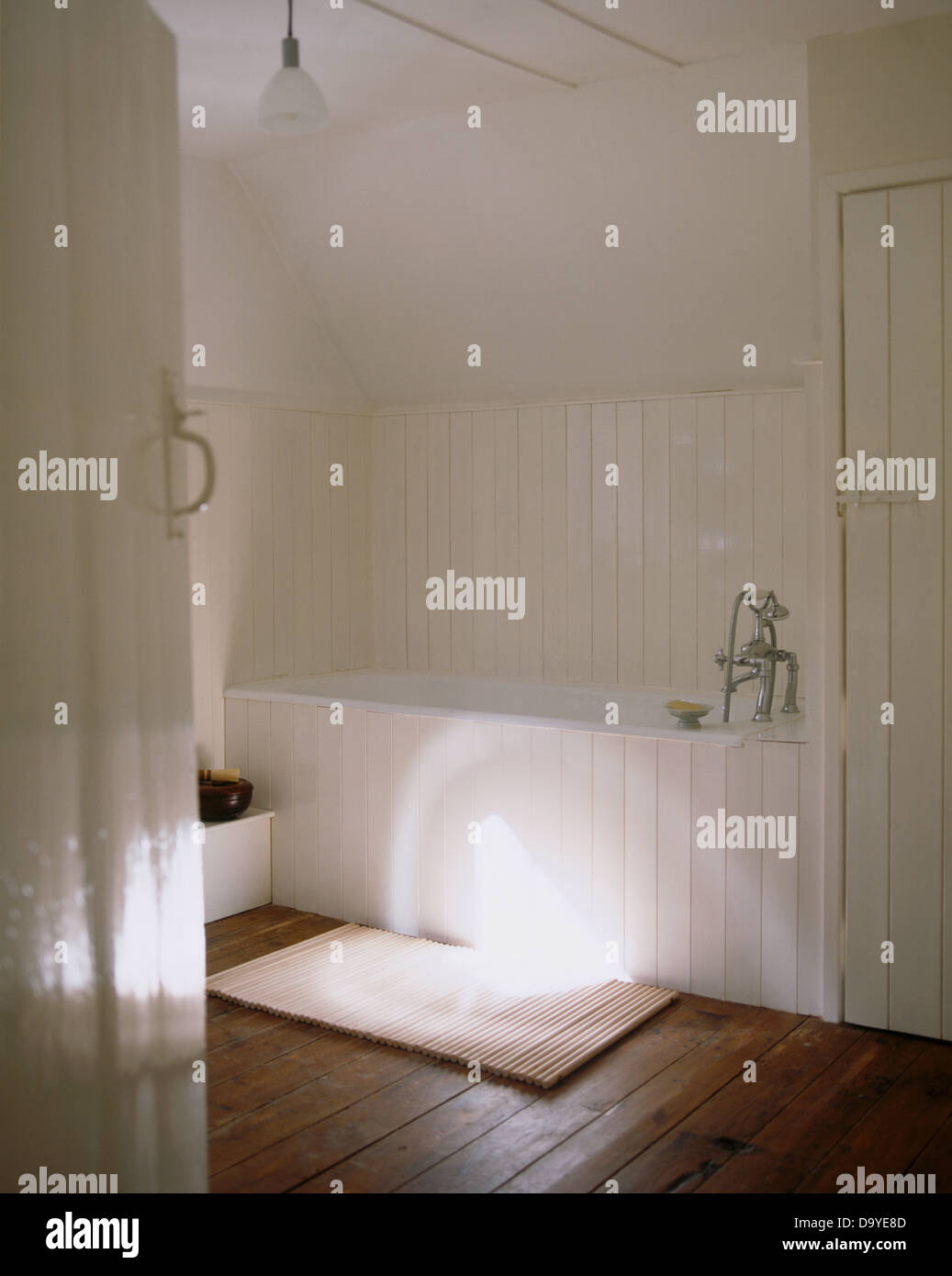 View through open door into a simple white bathroom with wooden floor and painted tongue+groove paneled walls and Stock Photo