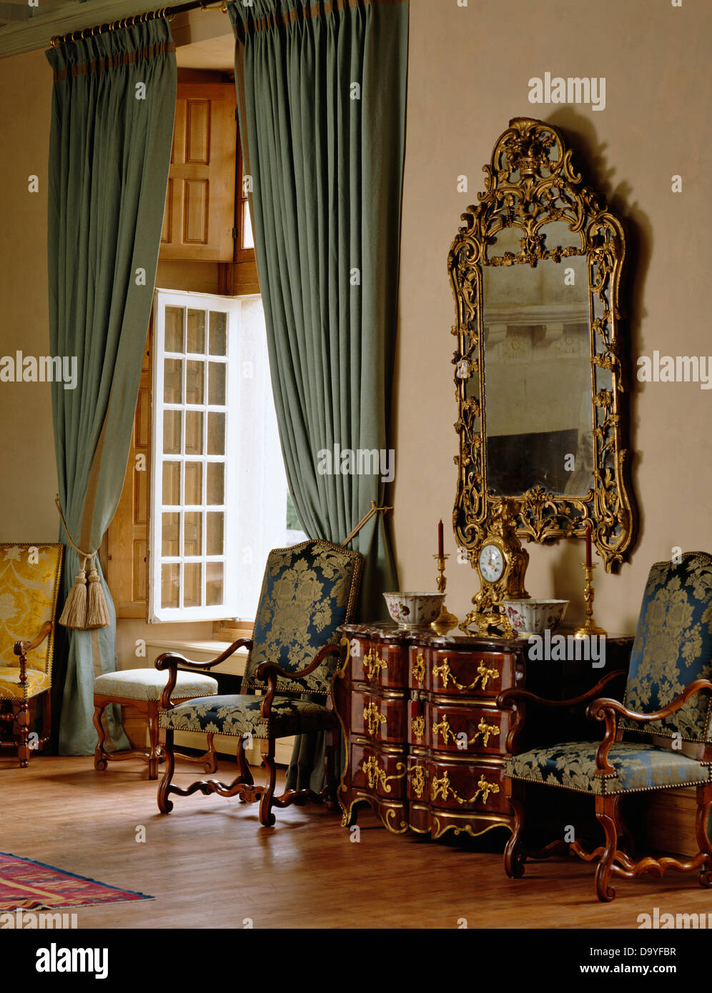 Ornate gilt-framed antique mirror above antique chest-of-drawers and ...