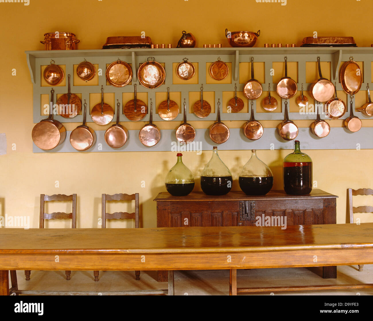 Rows of copper pots and pans on wooden wall rack above sideboard with large carboys of red wine in french country kitchen