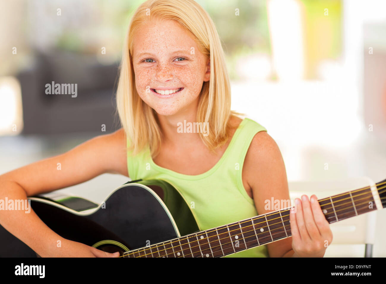 happy pre teen girl practicing guitar at home Stock Photo