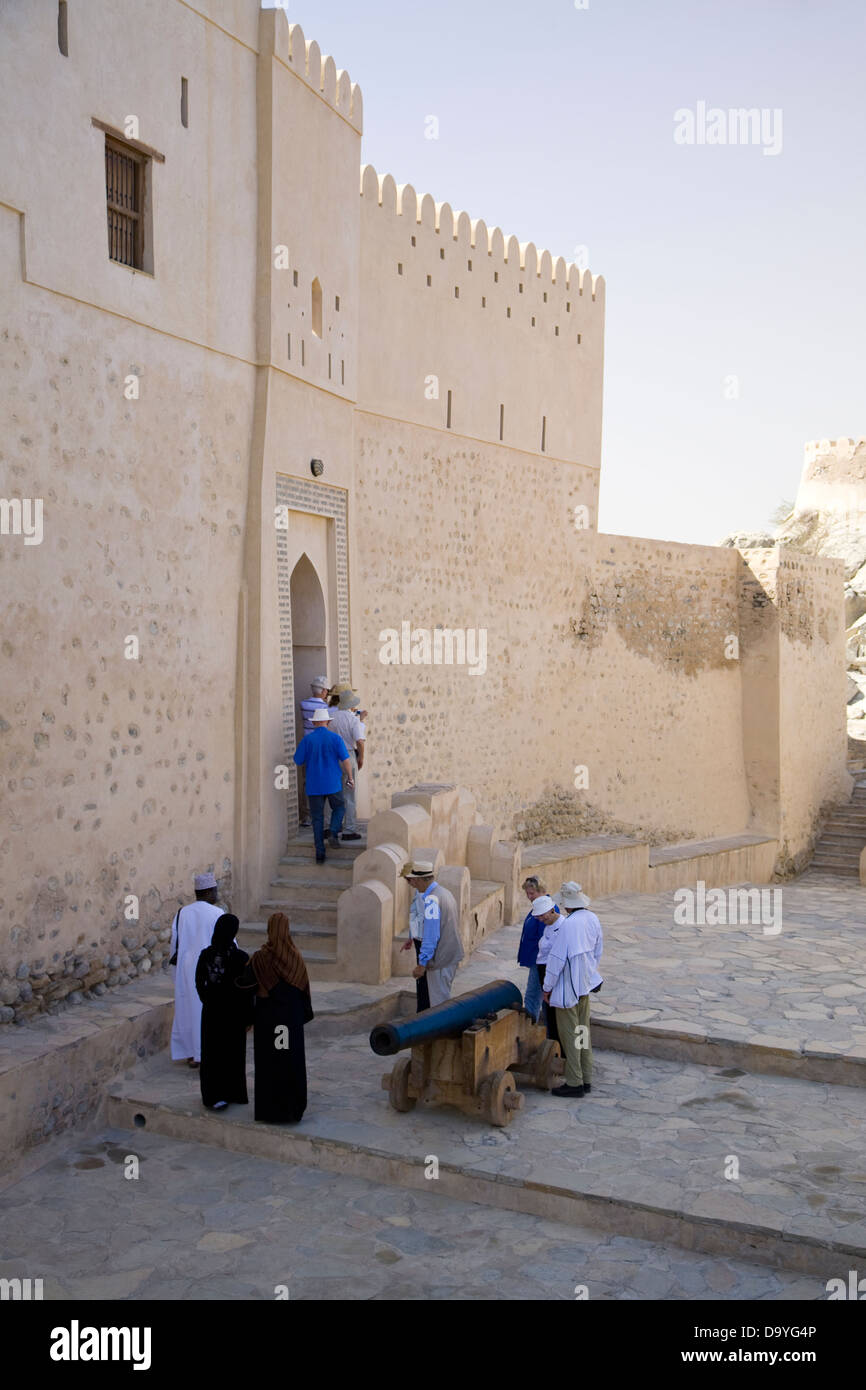 A tour group explores the well-preserved Fort of Nakhal, Nakhal, Oman - Stock Image