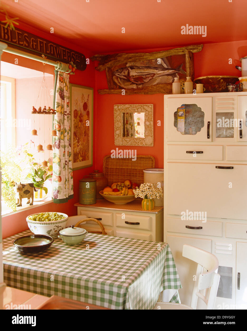 Green Checked Cloth On Table Beneath Window In Red Country Kitchen With  White Painted Fifties Cupboard